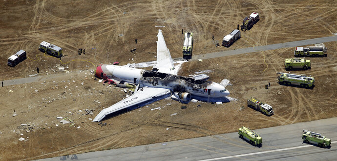 FILE - This July 6, 2013, file photo shows the wreckage of Asiana Flight 214 on the ground after it crashed at San Francisco International Airport in San Francisco. A San Francisco firefighter who says she was wrongly singled out for driving over a teen thrown from the wreckage of the 2013 airliner crash will receive $250,000 from the city to settle her lawsuit. The San Francisco Board of Supervisors approved the settlement in a vote Tuesday, Feb. 13, 2018. (AP Photo/Marcio Jose Sanchez, File)
