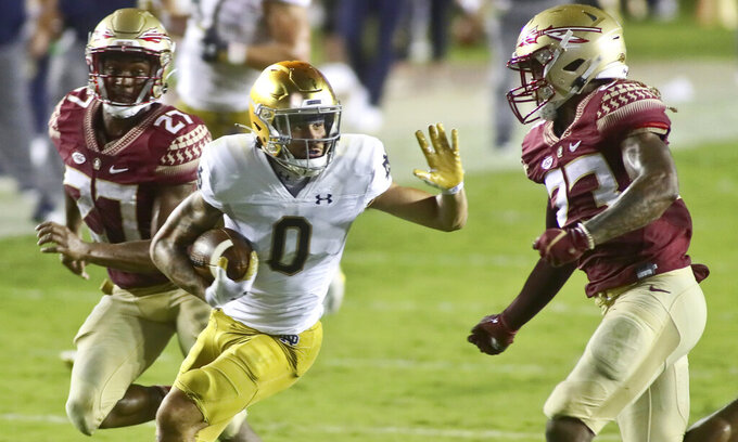 Notre Dame wide receiver Braden Lenzy (0) tries to stiff arm Florida State defensive back Sidney Williams (23) in the third quarter of an NCAA college football game Sunday, Sept. 5, 2021, in Tallahassee, Fla. (AP Photo/Phil Sears)