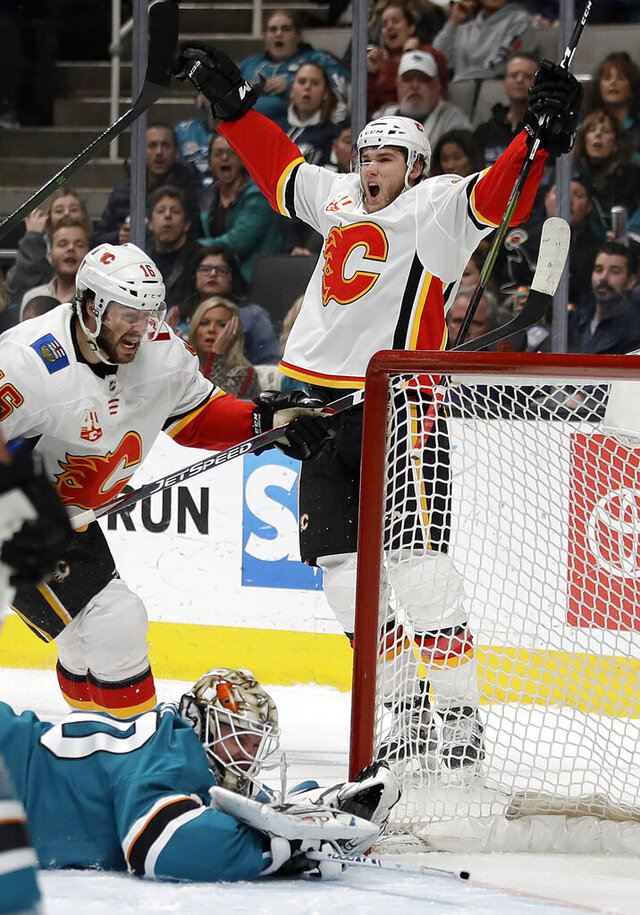 Calgary Flames' Mark Jankowski, top right, celebrates after scoring a goal against San Jose Sharks goalie Aaron Dell, bottom left, during the second period of an NHL hockey game, Monday, Feb. 10, 2020, in San Jose, Calif. (AP Photo/Ben Margot)