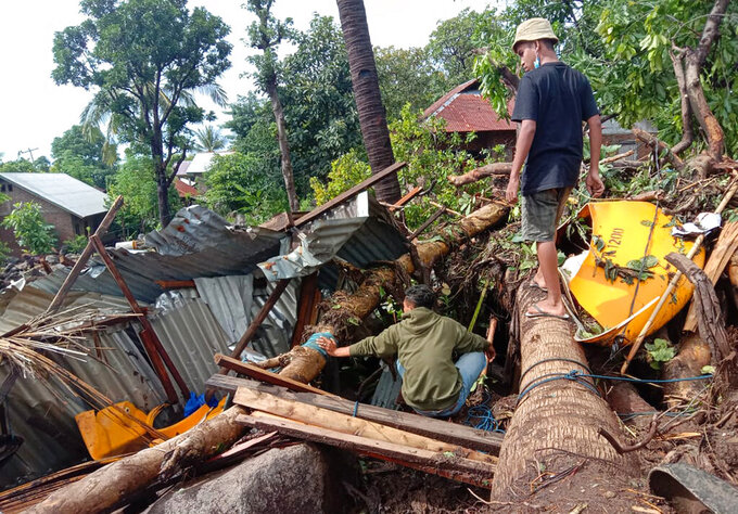 Indonesian scavenge usable items from the ruins of their house at a village hit by a landslide in Ile Ape Timur on Lembata Island, East Nusa Tenggara province, Indonesia, Monday, April 5, 2021. Multiple disasters caused by torrential rains in eastern Indonesia and neighboring East Timor have left a number of people dead or missing as rescuers were hampered by damaged bridges and roads and a lack of heavy equipment Monday. (AP Photo/Ricko Wawo)