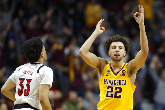 Minnesota guard Gabe Kalscheur (22) celebrates in front of Louisville forward Jordan Nwora (33) after making a three-point basket during a first round men's college basketball game in the NCAA Tournament, Thursday, March 21, 2019, in Des Moines, Iowa. (AP Photo/Charlie Neibergall)
