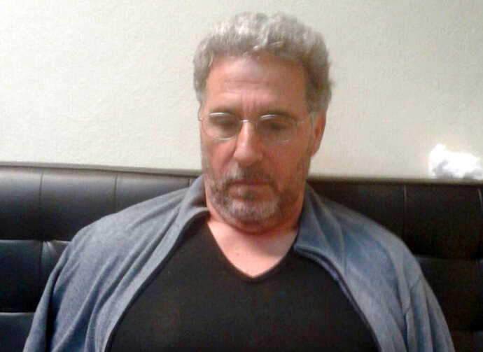 FILE - In this Sept. 3, 2017 file photo released by the Italian police, a man identified by police as longtime fugitive Rocco Morabito, looks down after being arrested at a hotel in Montevideo, Uruguay. The top Italian organized crime boss escaped during the night from the Uruguayan prison where he was awaiting extradition to Italy, Uruguay's interior ministry said Monday, June 24, 2019. (Italian Police via AP)