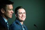 Newly signed Seattle Mariner Evan White, right, listens as Mariners general manager Jerry Dipoto speaks during a news conference at T-Mobile Park Monday, Nov. 25, 2019 in Seattle. (Andy Bao/The Seattle Times via AP)