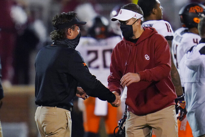 Oklahoma State coach Mike Gundy, left, and Oklahoma coach Lincoln Riley shake hands following an NCAA college football game in Norman, Okla., Saturday, Nov. 21, 2020. (AP Photo/Sue Ogrocki)