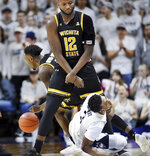 Connecticut's Alterique Gilbert (3) falls, hurting his previously injured shoulder, during the second half of the team'sNCAA college basketball game against Wichita State on Saturday, Jan. 26, 2019 in Storrs, Conn. Wichita State's Morris Udeze (12) defends. (AP Photo/Stephen Dunn)