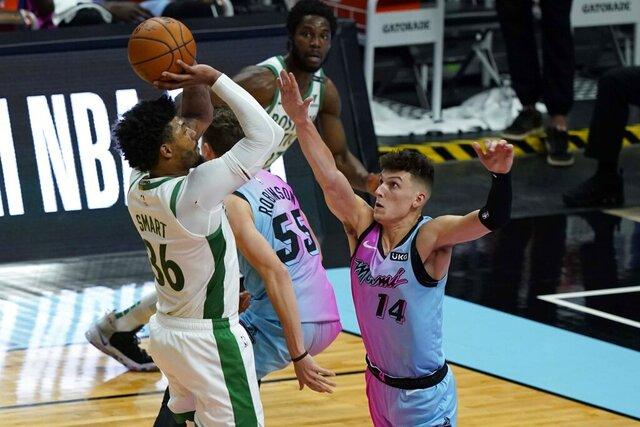Boston Celtics guard Marcus Smart (36) drives to the basket as Miami Heat guard Tyler Herro (14) defends during the first half of an NBA basketball game, Wednesday, Jan. 6, 2021, in Miami. (AP Photo/Marta Lavandier)