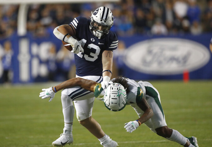BYU fullback Masen Wake (13) stiff arms a tackle by South Florida safety Matthew Hill (1) in the first half of an NCAA college football game Saturday, Sept. 25, 2021, in Provo, Utah. (AP Photo/George Frey)