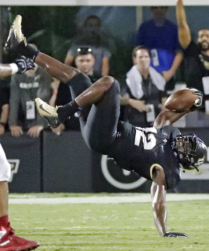 Central Florida linebacker Eric Mitchell is upended after intercepting a Florida Atlantic pass during the second half of an NCAA college football game, Friday, Sept. 21, 2018, in Orlando, Fla. (AP Photo/John Raoux)