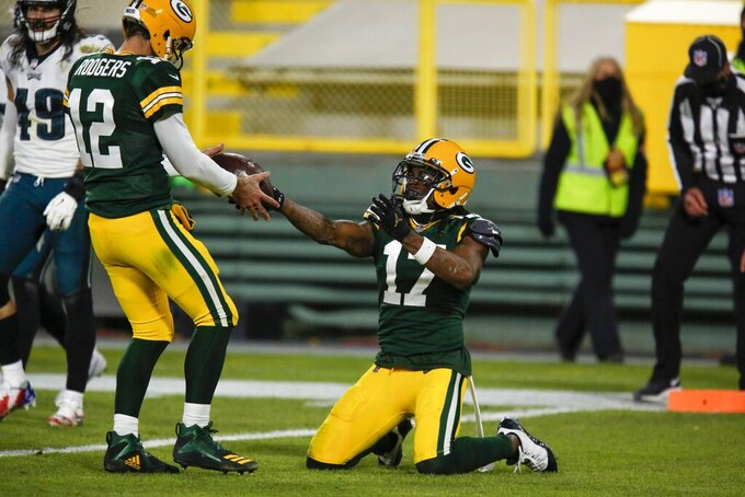Green Bay Packers' Davante Adams gives quarterback Aaron Rodgers the ball after catching a touchdown pass during the second half of an NFL football game against the Philadelphia Eagles Sunday, Dec. 6, 2020, in Green Bay, Wis. The pass was Aaron Rodgers' 400th career touchdown pass. (AP Photo/Matt Ludtke)