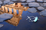 The Colosseum, that will be closed following the government's new prevention measures on public gatherings, is reflected in a puddle where a face mask was left, in Rome, Sunday, March 8, 2020. Italy announced a sweeping quarantine early Sunday for its northern regions, igniting travel chaos as it restricted the movements of a quarter of its population in a bid to halt the new coronavirus' relentless march across Europe. (Alfredo Falcone/LaPresse via AP)