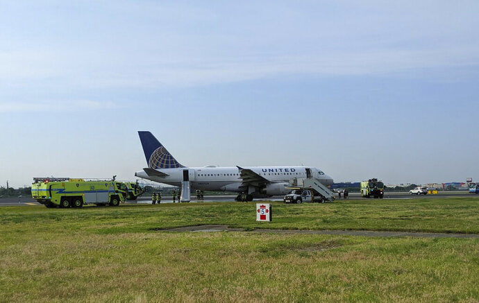 """This photo provided by John Murray shows a United flight sitting on the runway after making an emergency landing, Saturday, June 29, 2019 at Newark Liberty Airport in Newark, N.J. United said Flight 2098 heading from LaGuardia Airport in New York experienced problems upon takeoff just before 8 a.m. Saturday. The Port Authority of New York and New Jersey said it was """"hydraulics problems.""""   (John Murray via AP)"""