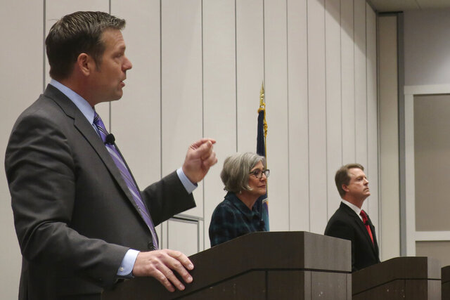 Former Kansas Secretary of State Kris Kobach, left, a Republican candidate, speaks during a debate for GOP candidates at a statewide Republican convention, Saturday, Feb. 1, 2020, in Olathe, Kan. Also participating are Kansas Senate President Susan Wagle, center, of Wichita, and U.S. Rep. Roger Marshall, of western Kansas. (AP Photo/John Hanna)
