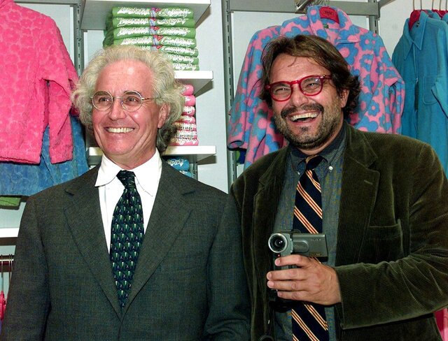 FILE - Luciano Benetton, left, and photographer Oliviero Toscani are shown in this Sept. 29, 1998 file photo. Oliviero Toscani made a career out of provocative photographs for Benetton, the Italian makers of colorful knitwear. But that decades-long relationship was severed  this week after Toscani made a remark that outraged the family members of victims in the deadly 2018 Genoa bridge collapse. (AP Photo/Luca Bruno/FILES)