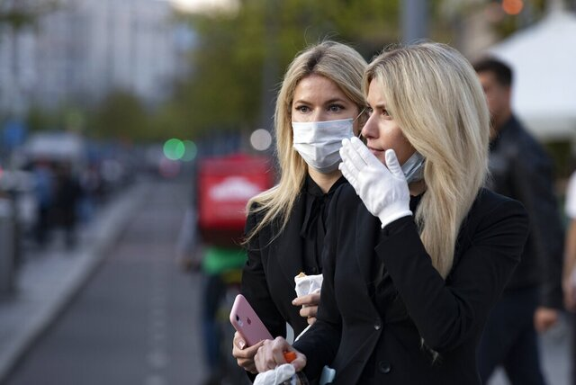 Two women wearing face masks against coronavirus as wait to cross the road in the center of in Moscow, Russia, Wednesday, Sept. 23, 2020. Russia confirmed over six and half thousand new Covid-19 cases Wednesday, bringing the country's official number of cases to 1,122,241 as the number of new infections across the country continues to rise. (AP Photo/Alexander Zemlianichenko)