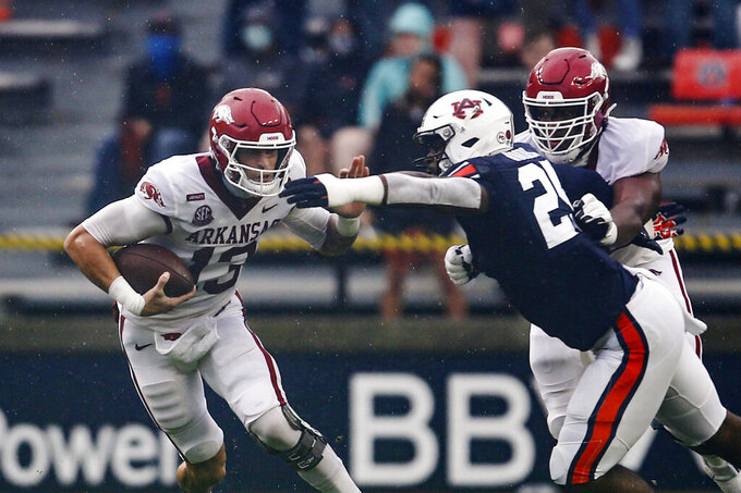 Arkansas quarterback Feleipe Franks (13) scrambles for yardage as Auburn defensive back Smoke Monday (21) tries to tackle him during the first quarter of an NCAA college football game on Saturday, Oct. 10, 2020, in Auburn, Ala. (AP Photo/Butch Dill)