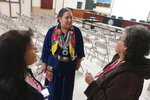 In this Jan. 14, 2020, photo, Navajo Nation lawmaker Amber Crotty, center, speaks to women about a family member who is missing in Tuba City, Ariz. People were gathered to talk not about women and girls who have disappeared or been killed, but men. It's a shift from a larger movement focused on Native American women, who face some of the nation's highest homicide, sexual violence and domestic abuse rates. (AP Photo/Felicia Fonseca)