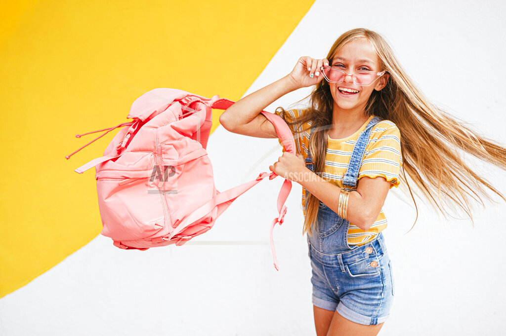 Happy girl with sunglasses and backpack spinning in front of wall
