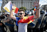 A protester shouts outside the government headquarters, in Bucharest, Romania, Friday, Aug. 10, 2018. Romanians who live abroad have begun an anti-government protest calling on the left-wing government to resign and an early election. (AP Photo/Andreea Alexandru)