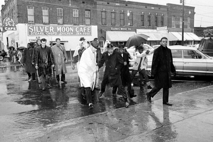 FILE - In this March 1, 1965 file photo Dr. Martin Luther King Jr. hops over a puddle as it rains in Selma, Ala. King led hundreds of African Americans to the court house in a voter registration drive. At front is civil rights worker Andrew Young, and at right, behind King is Rev. Ralph Abernathy. Today's protests across America against racial injustice are being watched closely by people who five decades ago faced jail cells, bloody assaults, snarling dogs and even potential assassination in the battle against institutional racism. Young, a King lieutenant, marvels at both the sizes and the spontaneity of the protests. The former Democratic congressman, Atlanta mayor and United Nations ambassador recalled activists spending three months to organize for a 1963 Birmingham, Alabama, campaign in which King and other protesters were jailed.    (AP Photo, File)