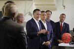 Utah Sen. Mitt Romney, center, speaks during a news conference with athletic directors from Utah colleges at the University of Utah Friday, Nov. 15, 2019, in Salt Lake City. Romney says he supports efforts to allow college athletes to profit from their name and image because he wants to help poor students who may never become professional athletes. (AP Photo/Rick Bowmer)