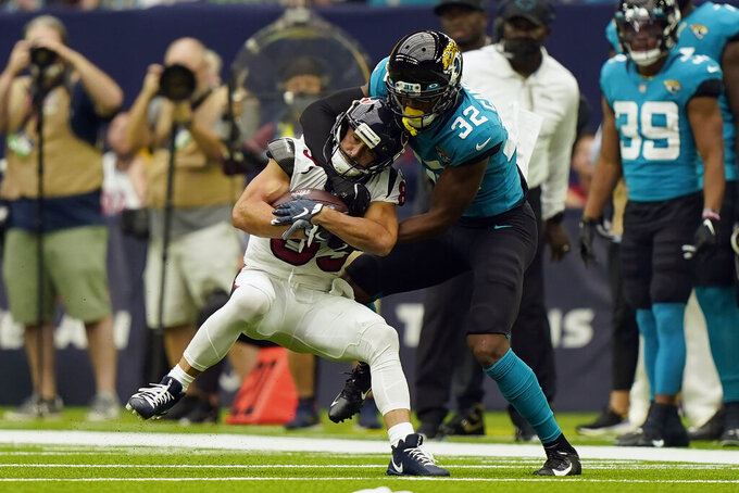 Houston Texans wide receiver Danny Amendola, left, catches a pass as Jacksonville Jaguars cornerback Tyson Campbell (32) tackles him during the first half of an NFL football game Sunday, Sept. 12, 2021, in Houston. (AP Photo/Eric Christian Smith)