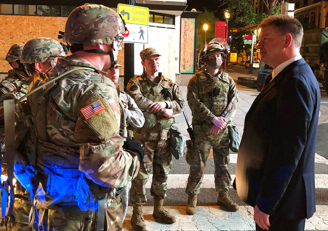 In this Wednesday, June 3, 2020, photo  Acting Drug Enforcement Administrator Timothy Shea, right,  visits with Indiana National Guard soldiers at a checkpoint in Washington. (AP Photo/Mike Balsamo)