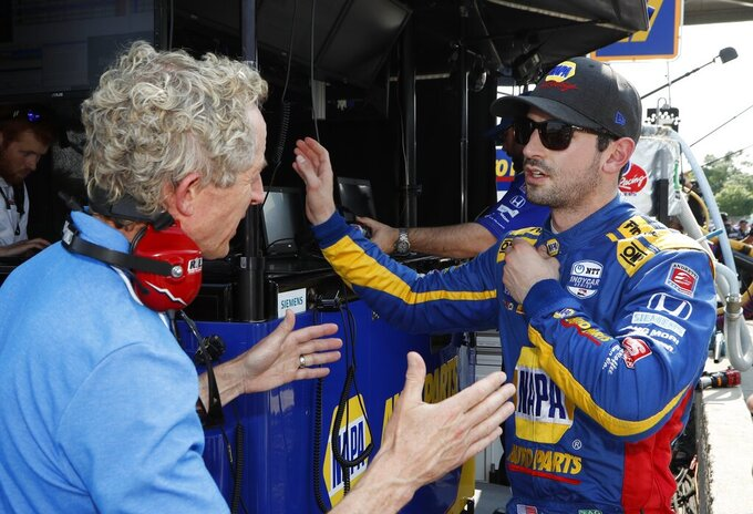 Alexander Rossi, right, talks to a media member after a practice session for the first race of the IndyCar Detroit Grand Prix auto racing doubleheader, Friday, May 31, 2019, in Detroit. (AP Photo/Carlos Osorio)