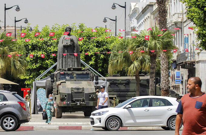 Tunisians walk past a military armored personnel carrier at Habib Bourguiba avenue in Tunis, Tunisia, Friday, July 30, 2021. Days of political turmoil in Tunisia over the economy and the coronavirus have left its allies in the Middle East, Europe and the United States watching to see if the fragile democracy will survive. (AP Photo/Hassene Dridi)