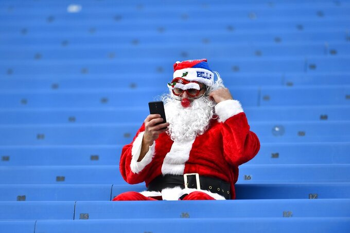 A Buffalo Bills fan dressed in a Santa suit waits for the start of an NFL football game between the Buffalo Bills and the Denver Broncos, Sunday, Nov. 24, 2019, in Orchard Park, N.Y. (AP Photo/Adrian Kraus)