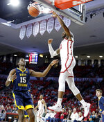 Oklahoma's Rashard Odomes (1) dunks beside West Virginia's Lamont West (15) during an NCAA college basketball game in Norman, Okla., Saturday, March 2, 2019. (Bryan Terry/The Oklahoman via AP)