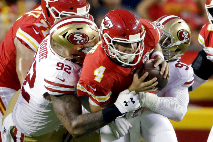 Kansas City Chiefs quarterback Chad Henne (4) is sacked by San Francisco 49ers defensive lineman Damontre Moore (92) and defensive end Arik Armstead (91) during the first half of an NFL preseason football game in Kansas City, Mo., Saturday, Aug. 24, 2019. (AP Photo/Charlie Riedel)