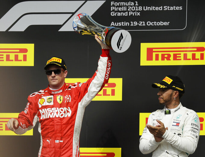 """FILE - In this Oct. 21, 2018, file photo, Ferrari driver Kimi Raikkonen, of Finland, holds the trophy after winning the Formula One U.S. Grand Prix auto race at the Circuit of the Americas, as third-placed Mercedes driver Lewis Hamilton, right, of Britain, looks on, in Austin, Texas. Formula One expects to race the U.S. Grand Prix at the Circuit of the Americas for """"many years to come,"""" a series official said Tuesday, May 28, 2019, despite the track's failed effort to secure $25 million in Texas public money it was denied in 2018. Sean Bratches, F1's managing director of commercial operations, suggested the series remains confident in the Texas race's' financial security. (AP Photo/Eric Gay, File)"""