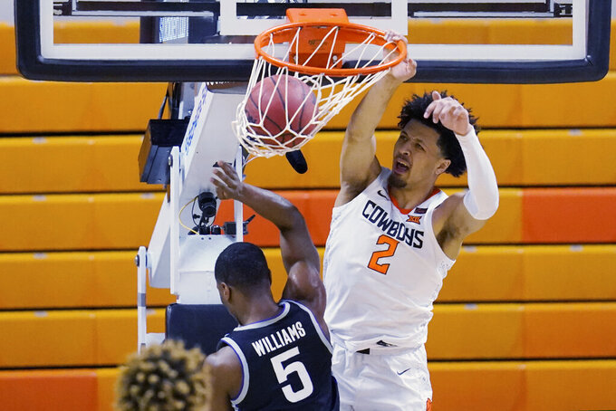 Oklahoma State guard Cade Cunningham (2) dunks in front of Kansas State guard Rudi Williams (5) in the first half of an NCAA college basketball game Saturday, Feb. 13, 2021, in Stillwater, Okla. (AP Photo/Sue Ogrocki)
