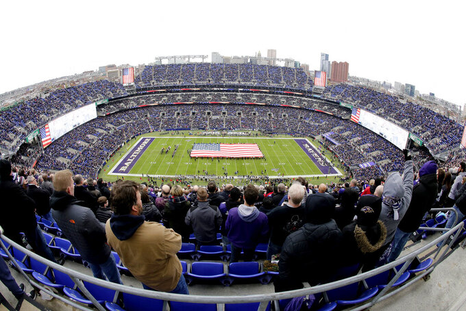 U.S. service members hold a large flag on the field at M&T Bank Stadium as part of the Baltimore Ravens' Salute to Service prior to an NFL football game against the Houston Texans, Sunday, Nov. 17, 2019, in Baltimore. (AP Photo/Julio Cortez)