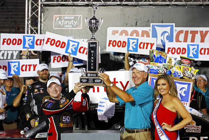 Tyler Reddick hoists the trophy with Steve Smith, president and CEO of Food City, after winning the NASCAR Xfinity Series auto race Friday, Aug. 16, 2019, in Bristol, Tenn. (AP Photo/Wade Payne)
