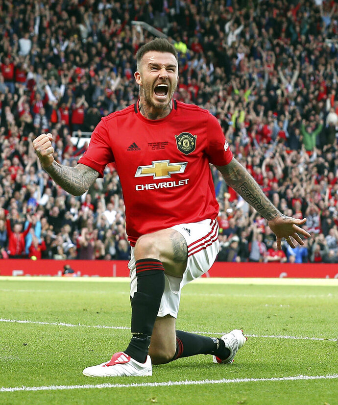 Manchester United Legend's David Beckham celebrates scoring his side's fifth goal of the game during the legends match between Manchester United Legends and Bayern Munich Legens at Old Trafford, Manchester, England, Sunday, May 26, 2019. (Martin Rickett/PA via AP)