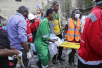 Rescue workers carry a baby rescued from the rubble of a building that collapsed in Tasia Embakasi, an east neighbourhood of Nairobi, Kenya on Friday Dec. 6, 2019. A six-story building collapsed in Kenya's capital on Friday, officials said, with people feared to be trapped in the debris. Police say people have been rescued by residents using their bare hands. (AP Photo/Khalil Senosi)