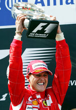 FILE - In this July 16, 2006 file photo, Ferrari's F1 driver Michael Schumacher, of Germany, raises the trophy after winning the French Formula One Grand Prix at the Magny-Cours circuit, central France.  Schumacher's family, in a statement Wednesday, Jan. 2, 2019, has asked for understanding as it continues to keep details of his health private ahead of the seven-time Formula One champion's 50th birthday. Schumacher suffered serious head injuries in an accident while he was skiing with his teenage son Mick in the French Alps at Meribel on Dec. 29, 2013. (AP Photo/Remy de la Mauviniere, File)