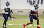 Tennessee Titans running back Derrick Henry, right, runs with the ball attached to a tether held by running back David Fluellen (32) during an organized team activity at the Titans' NFL football training facility Thursday, May 30, 2019, in Nashville, Tenn. (AP Photo/Mark Humphrey)