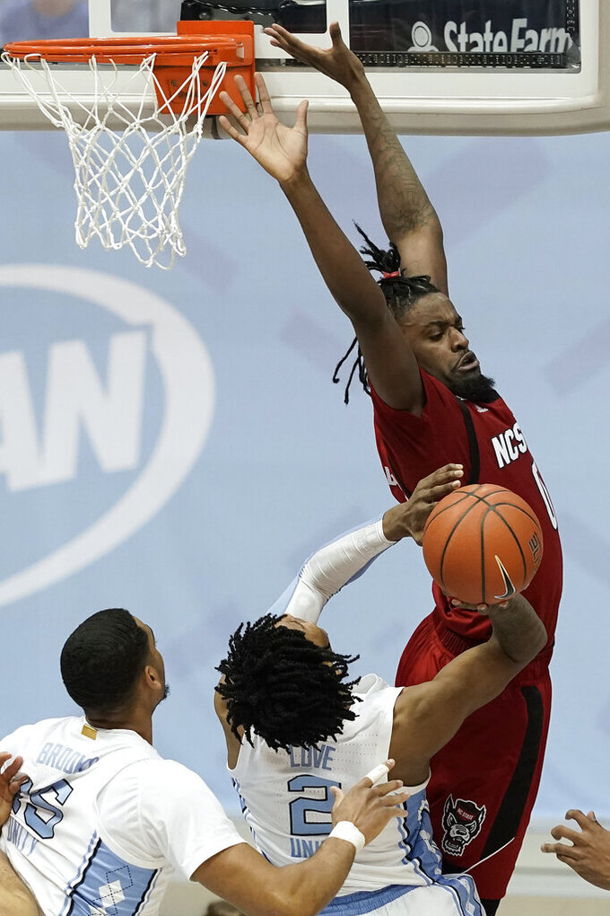 North Carolina State forward DJ Funderburk defends against North Carolina guard Caleb Love (2) during the second half of an NCAA college basketball game in Chapel Hill, N.C., Saturday, Jan. 23, 2021. (AP Photo/Gerry Broome)