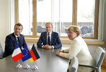 French President Emmanuel Macron, left, European Council President Donald Tusk, center, and German Chancellor Angela Merkel meet on the sidelines of an EU summit in Brussels, Thursday, June 20, 2019. European Union leaders meet for a two-day summit to begin the process of finalizing candidates for the bloc's top jobs. (Kenzo Tribouillard, Pool Photo via AP)