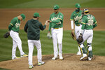 Oakland Athletics pitcher Sean Manaea, center, hands the ball to manager Bob Melvin as he is removed in the fourth inning of a baseball game against the Texas Rangers Wednesday, Aug. 5, 2020, in Oakland, Calif. (AP Photo/Ben Margot)