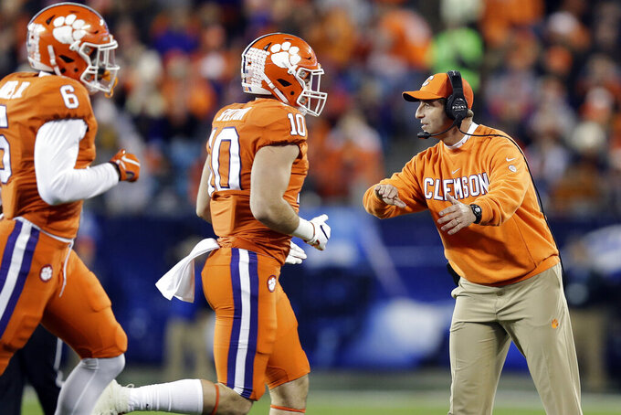 Clemson head coach Dabo Swinney directs his players during the first half of the Atlantic Coast Conference championship NCAA college football game against Virginia in Charlotte, N.C., Saturday, Dec. 7, 2019. (AP Photo/Gerry Broome)