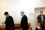 Israeli Prime Minister Benjamin Netanyahu, center, wearing a face mask in line with public health restrictions due to the coronavirus pandemic, enters the court room with his lawyer as his corruption trial opens at the Jerusalem District Court, Sunday, May 24, 2020.  He is the country's first sitting prime minister ever to go on trial, facing charges of fraud, breach of trust, and accepting bribes in a series of corruption cases stemming from ties to wealthy friends. (Ronen Zvulun/ Pool Photo via AP)