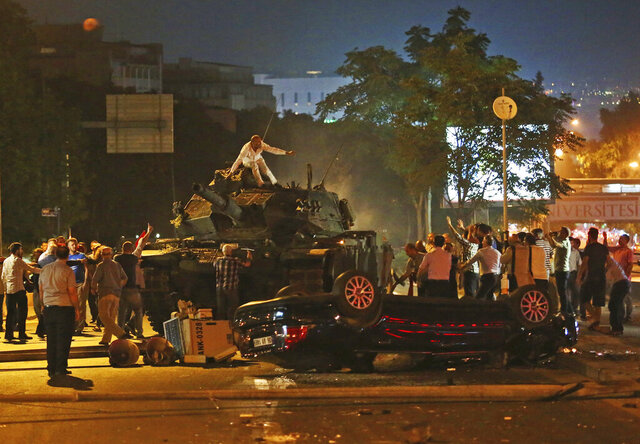 FILE - In this Saturday, July 16, 2016 file photo, tanks move into position as Turkish people attempt to stop them, in Ankara, Turkey. Turkey is marking the fourth anniversary of the July 15 failed coup attempt against the government on Wednesday July 15, 2020, with ceremonies and events remembering its victims. (AP Photo/File)