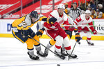 Nashville Predators defenseman Ben Harpur (17) and Detroit Red Wings right wing Anthony Mantha (39) chase a loose puck in the second period of an NHL hockey game Tuesday, April 6, 2021, in Detroit. (AP Photo/Paul Sancya)