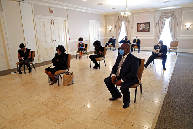 FILE - In this April 22, 2020, file photo, friends and family of Larry Hammond who were among only 10 mourners allowed, sit in chairs spaced for social distancing, during his funeral at Boyd Funeral Home in New Orleans. (AP Photo/Gerald Herbert, File)