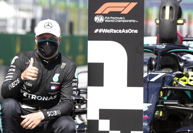 Mercedes driver Valtteri Bottas of Finland, wearing a mask against the spread of the coronavirus, poses after he clocked the fastest time during the qualifying session at the Red Bull Ring racetrack in Spielberg, Austria, Saturday, July 4, 2020. The Austrian Formula One Grand Prix will be held on Sunday. (Mark Thompson/Pool via AP)