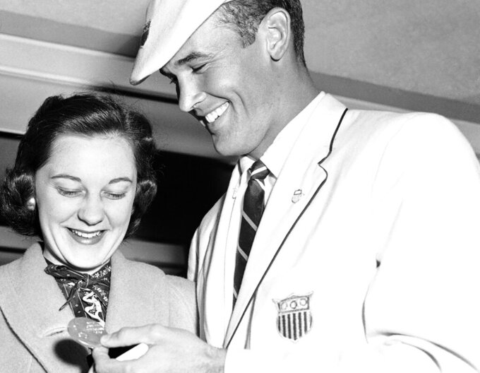 FILE - In this Dec. 8, 1956, file photo, Bobby Joe Morrow, right, the spirit champion of the just-concluded Olympic Games in Melbourne, Australia, shows one of his three gold medals to his wife, Joann, upon his arrival by air in Los Angeles. Morrow, the Texas sprinter who won three gold medals in the 1956 Melbourne Olympics while a student at Abilene Christian University, died Saturday, May 30, 2020. He was 84. (AP Photo/HF, File)