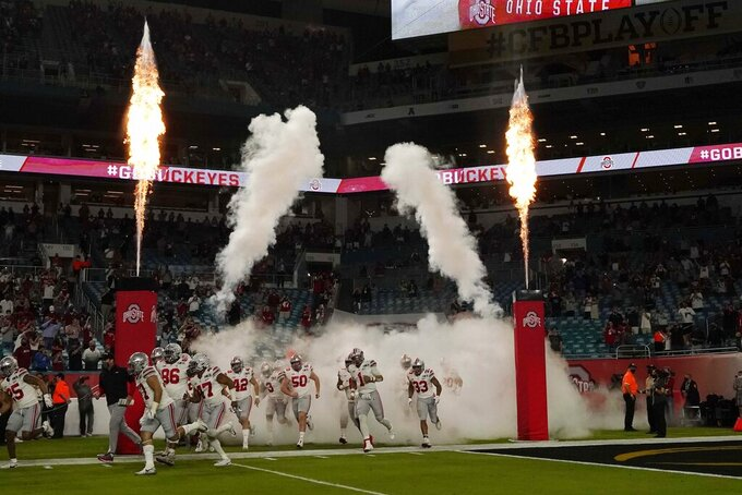 Ohio State players runs onto the field for the first half of an NCAA College Football Playoff national championship game against Alabama, Monday, Jan. 11, 2021, in Miami Gardens, Fla. (AP Photo/Chris O'Meara)